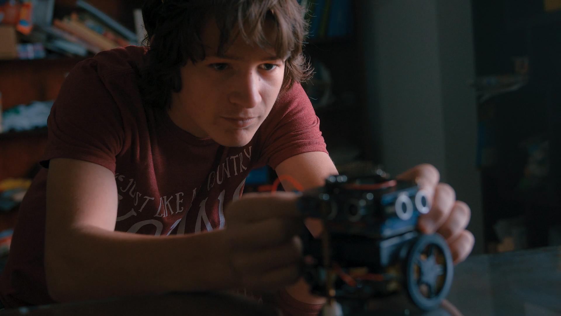 A robotics student at Quest Forward Academy Omaha examines his work.